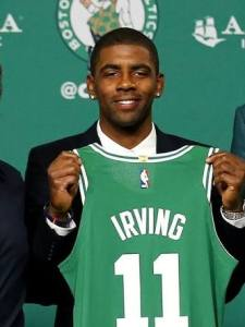 Kyrie Irving holding his official jersey for Boston Celtics